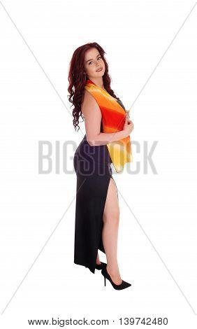 A lovely young woman in a black long dress and colorful scarf standing in profile isolated for white background.