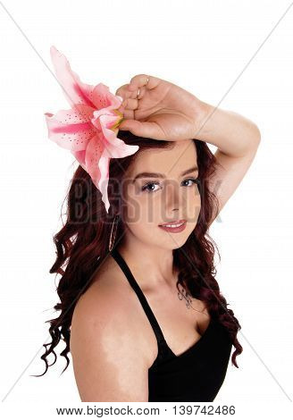 A closeup portrait of a beautiful young woman holding a pink lilly on her head isolated for white background.