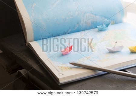 planning vacation trip, paper boats on the map