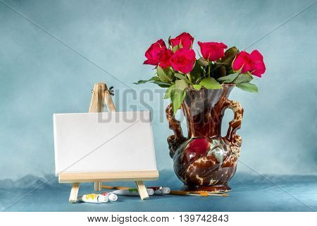 Still-life with a bouquet of roses, easel and paints.