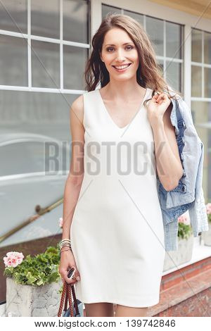 Happy young woman with brown hair outdoors. Model smiling and looking at camera