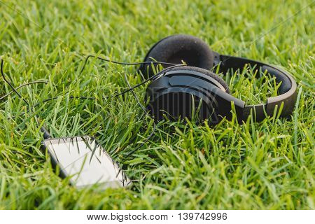 Black Smartphone and Headphones on the Green Grass. Techbology Concept