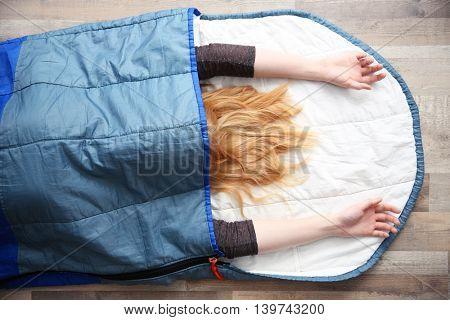 Beautiful woman lying in blue sleeping bag on wooden floor