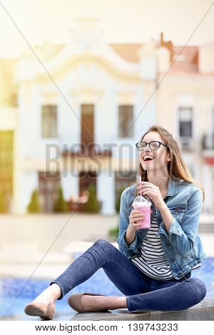 Attractive woman sitting on fountain with fruit smoothie