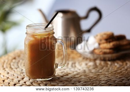 Iced coffee in glass jar on wicker table
