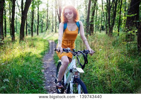 Young redhead woman in sunglasses riding a bike in the city park