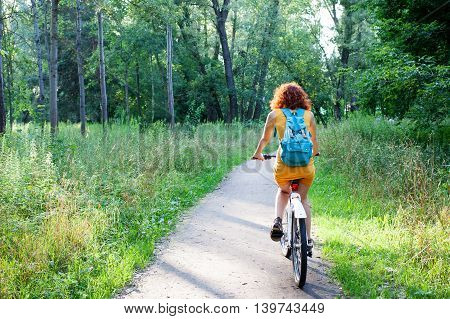 Woman riding a bike on the path in the city park view from the back