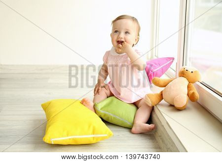 Baby sitting with teddy bear and pillows in room