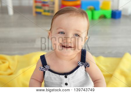 Happy baby girl sitting in child room