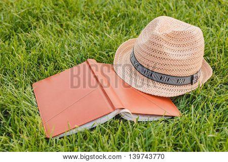 Hat, Book, Notebook on a Green Grass