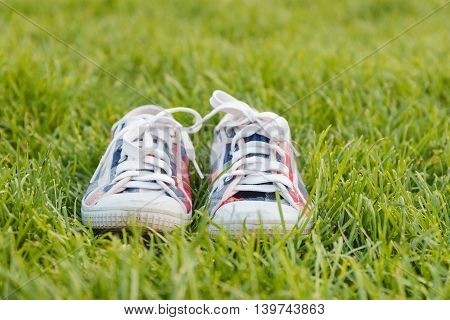 Youth Sneakers on Grass During Sunny Serene Summer Day