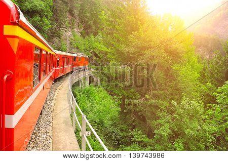 Passenger train moves from Chur to Arosa at sunset. Switzerland.