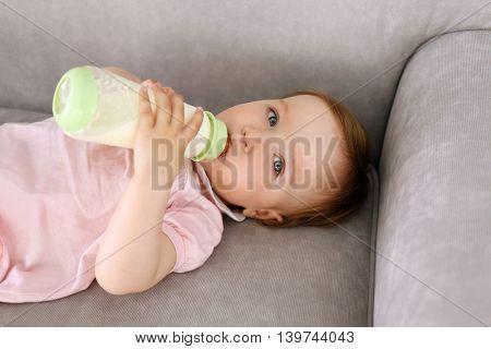 Baby drinking milk on sofa