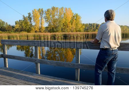 Middle-Aged Man Enjoying the Fall Colors Reflected in a Lake
