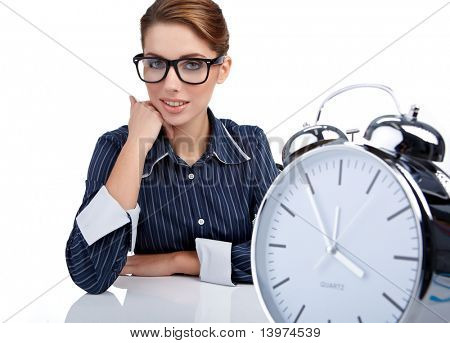Secretary  woman at her desk at the end of the day . clock concept