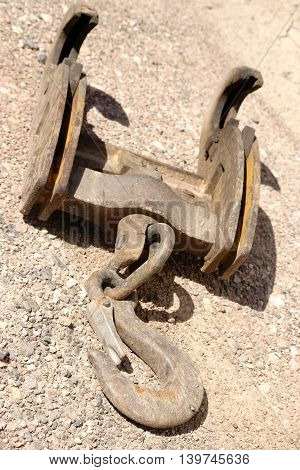 The close-up of a crane hook placed on a gravel bed.