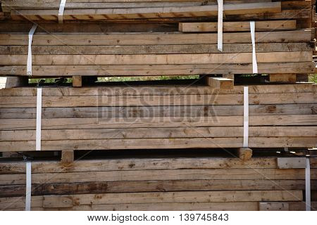 A stack of wooden boards tied together at a construction site.