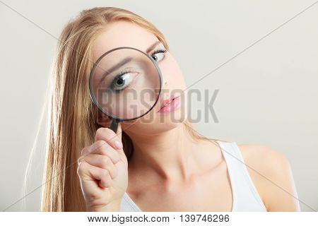 Investigation exploration education concept. Closeup woman face girl holding on eye magnifying glass loupe