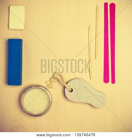 Foot care. Pedicure accessories set tools on wooden board background top view border frame with copy space
