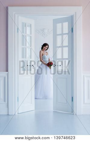 Fashion photo of a beautiful bride in the light room next to the door.