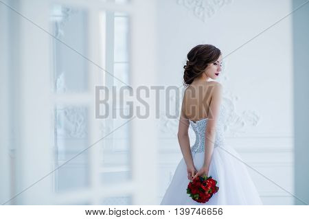 Fashion photo of a beautiful bride with flowers bouquet in her hands at the light room next to the doors.