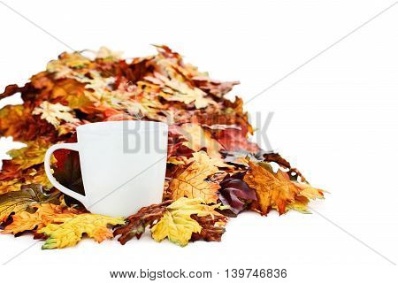 Hot cup of coffee surrounded by colorful autumn leaves isolated against a white background with light shadow and shallow depth of field.