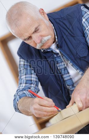 an elderly carpenter at work