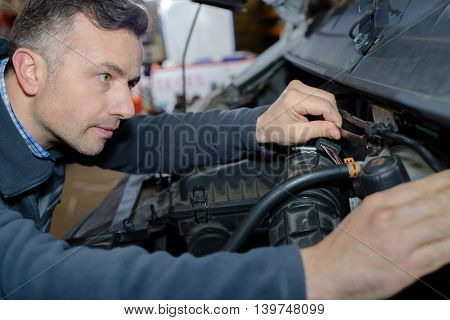 a closeup of a mechanic working on engine