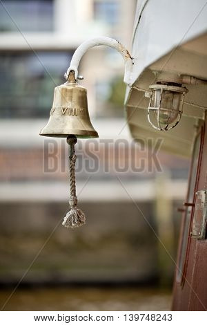 golden boat bell on a ship. background out of focus.