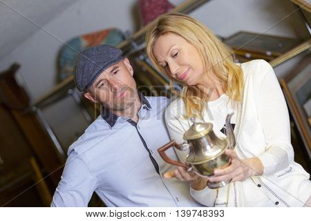couple chooses teapot in the cookware section at auction