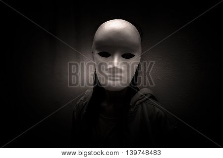 Dark doctrine,Mysterious woman wearing white mask,Scary background for book cover