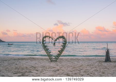 Palm Branches Tied Into The Shape Of A Heart On The Beach.