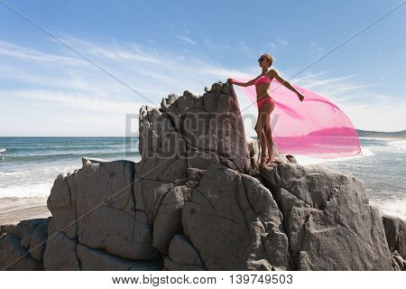Young slender woman on the sea rocky shore in a pink swimming suit and a pink fabric fluttering in the wind.