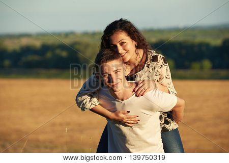 holidays, hiking, love and friendship concept - smiling couple having fun over evening sky background, summer season, girl riding on man back