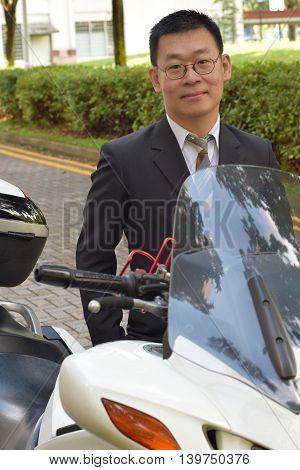 An asian business man standing besides a motor bike