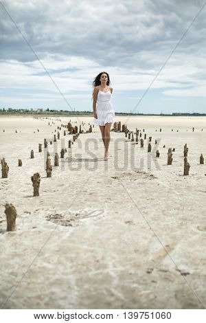 Cute barefoot girl walks on the sand on the cloudy sky background. She wears white dress. She looks in front of herself. There are wooden pillars on the sand on the sides of the girl. Outdoors. Vertical.