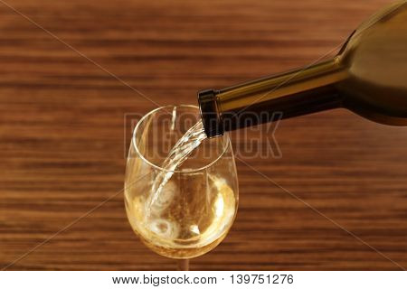 White wine pouring in glass on wooden background