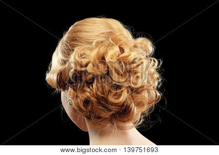 Portrait of young woman with elegant hairstyle on dark background