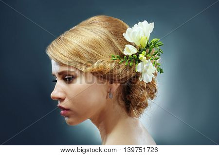 Portrait of young woman with elegant hairstyle on grey background
