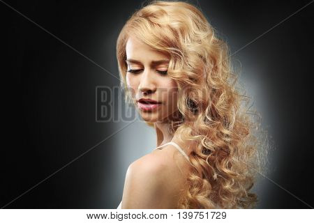 Portrait of young woman with blonde hair on dark background
