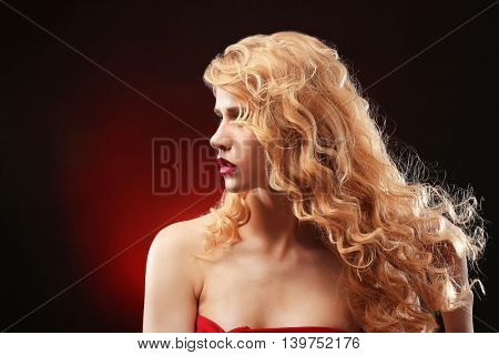 Portrait of young woman with blonde hair on dark red background