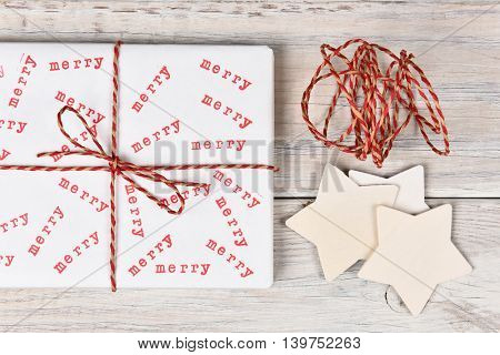 Christmas present stamped with the word Merry. High angle shot with  twine and wood stars.