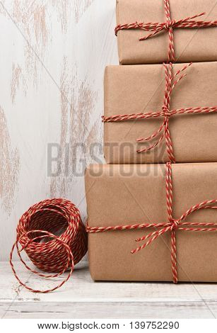 Closeup of three plain brown paper wrapped Christmas presents with twine.