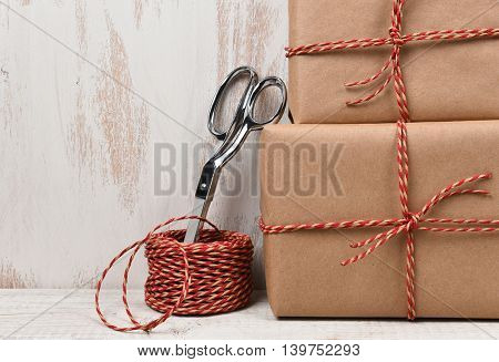 Closeup of two plain brown paper wrapped Christmas presents with scissors and twine.