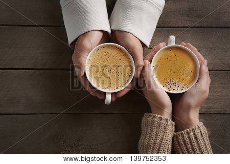 Lovely couple holding cup of coffee in hands on wooden background
