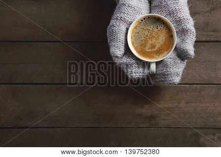 Female hands in knitted gloves holding cup of coffee on wooden background