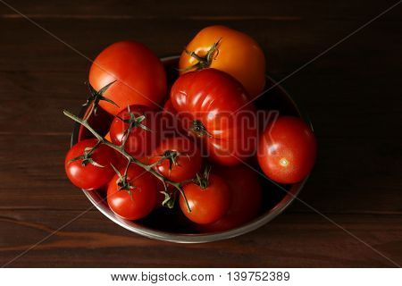 Different tomatoes in metallic bowl on dark background