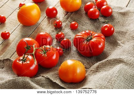 Rustic composition of tomatoes and sackcloth on wooden background