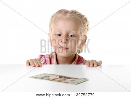 Funny little girl hiding behind white table and looking at dollar