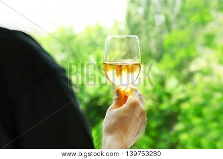 Man holding glass of wine on blurred natural background